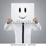 stock-photo-young-businessman-holding-white-card-with-a-happy-face-on-it-isolated-on-gray-background-118731460